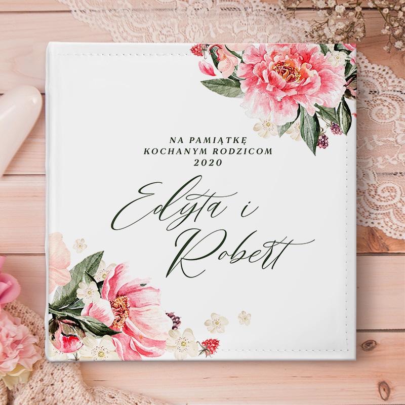 Album na zdjęcia ślubne z personalizowaną okładką na której znajduje się kwiatowa dekoracja, w środku której wkomponowane są imiona pary młodej, nad którymi znajdzie się dedykacja dla rodziców. Okładka ma jasny kolor.