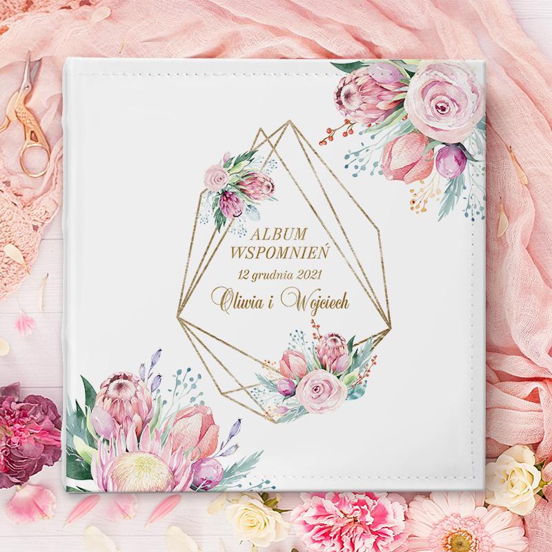 Album na zdjęcia ślubne z dekoracyjną okładką z geometryczną ramą i kwiatami oraz dedykacją i imionami pary młodej. Album do wklejania zdjęć w środku z pergaminem, który zabezpiecza strony.