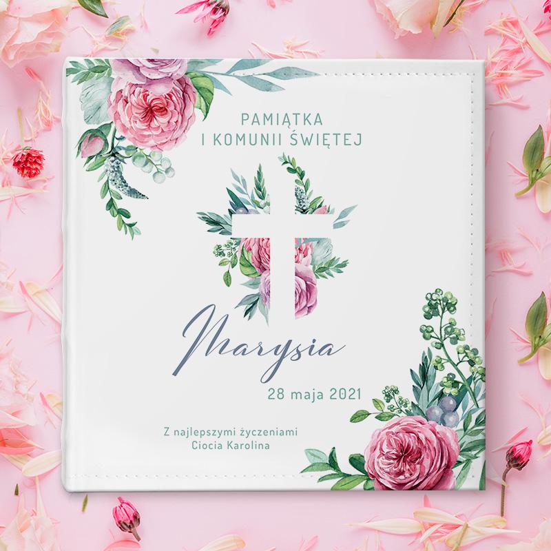 Personalizowany album z dekoracyjnymi różami na rogach okładki i krzyżem na tle kwiatów i dedykacją z imieniem i datą komunii.