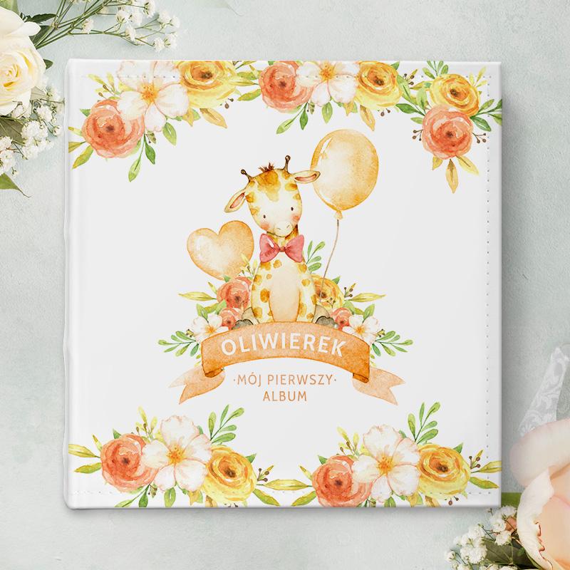 Album na fotografie z imieniem dziecka i dedykacją oraz uroczą żyrafą na froncie albumu, która ubrana jest w elegancką muszkę oraz wokół której znajdują się baloniki.