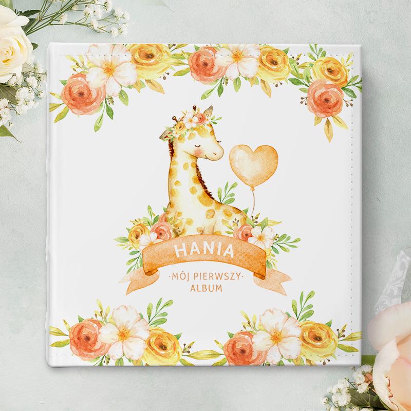 Personalizowany album na zdjęcia z motywem dziewczynki żyrafy w ozdobnym wianku i z balonikiem. Na górze i dole okładki są również motywy kwiatowe.
