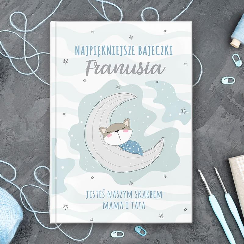 Książka z bajkami dla dzieci z personalizowaną okładką z imieniem dziecka, dedykacją oraz podpisem. Na froncie znajduje się również obrazek z misiem, który błogo śpi na księżycu.