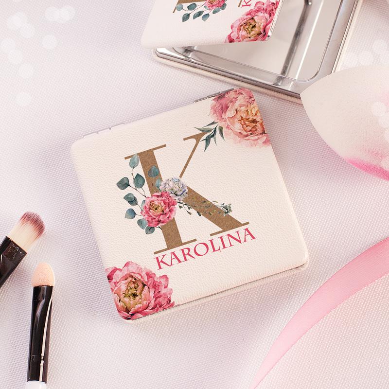 Kieszonkowe lusterko z kobiecym wzorem w postaci inicjału, imienia oraz różowych kwiatów. Lusterko jest rozkładane i otwiera się.