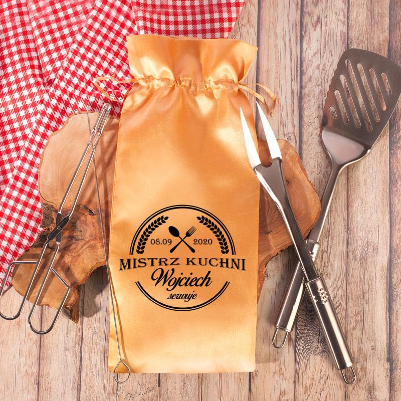 Zestaw narzędzi na grilla, które zapakowane są w satynowy, złoty woreczek z personalizowanym napisem oraz dekoracyjną grafiką z nożem i widelcem.