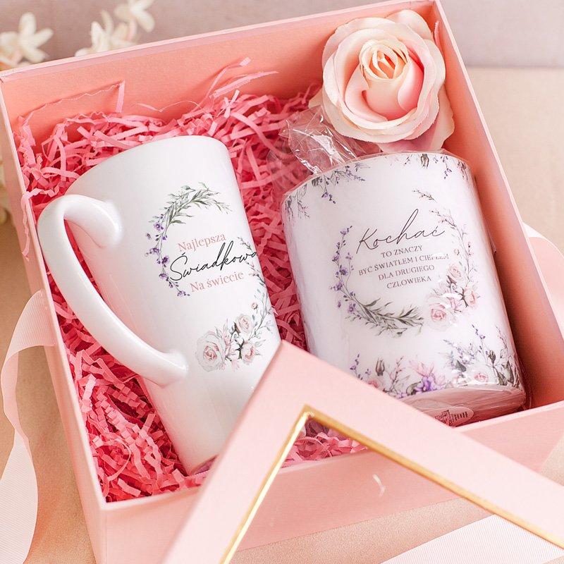 Różowe pudełko z kubkiem i świecą w środku, na różowym konfetti
