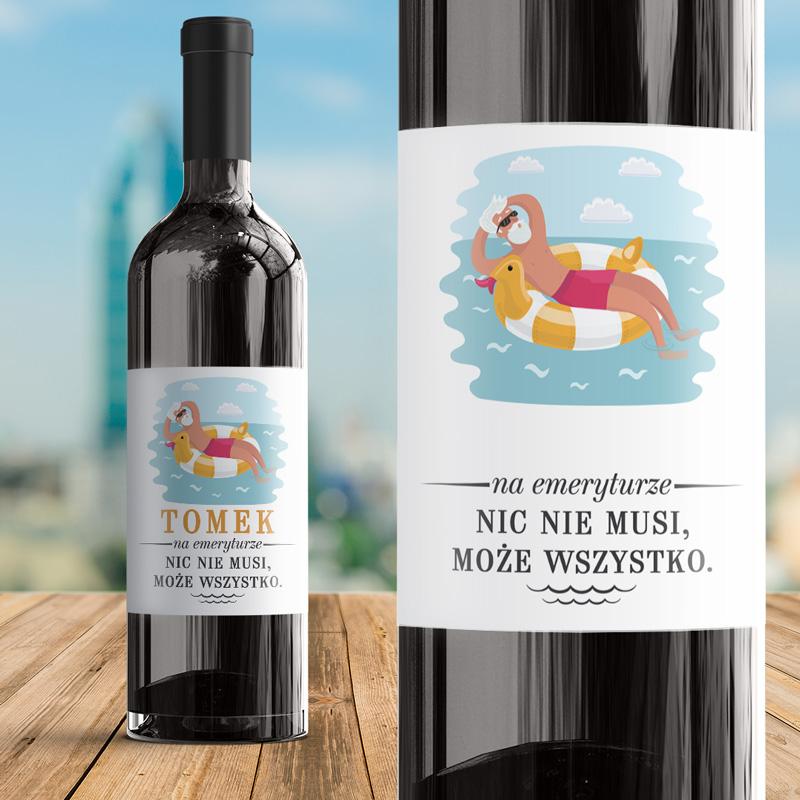Etykieta na wino naklejka z postacią starszego pana, który wyleguje się na dmuchanym kole, na środku jeziora. Poniżej wakacyjnej grafiki jest miejsce z dedykacją i dopiskiem imiennym oraz podpisem od kogo jest wino.