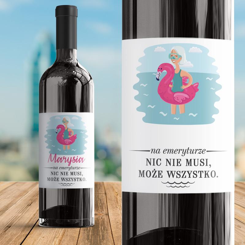 Samoprzylepna etykieta na butelce z winem. Kolorowy obrazek przedstawia kobietę na kole flamingu, która właśnie kąpie się w wodzie. Pod obrazkiem jest miejsce na imię oraz podpis od kogo jest prezent. Etykieta ma białe tło i różowo-niebieskie nadruki.