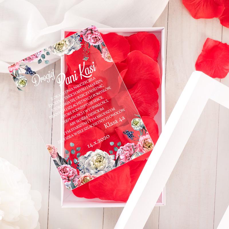 Dekoracyjna kartka z pleksi z życzeniami na Dzień Nauczyciela oraz płatkami róż w ozdobnym, białym pudełeczku.