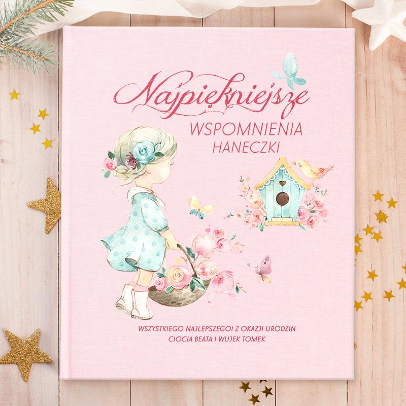 Album do wklejania zdjęć z różową, materiałową okładką z kolorowym nadrukiem dziewczynki z kwiatami oraz ptaszka w karmniku. Na okładce albumu jest miejsce na imię dziecka i podpis.