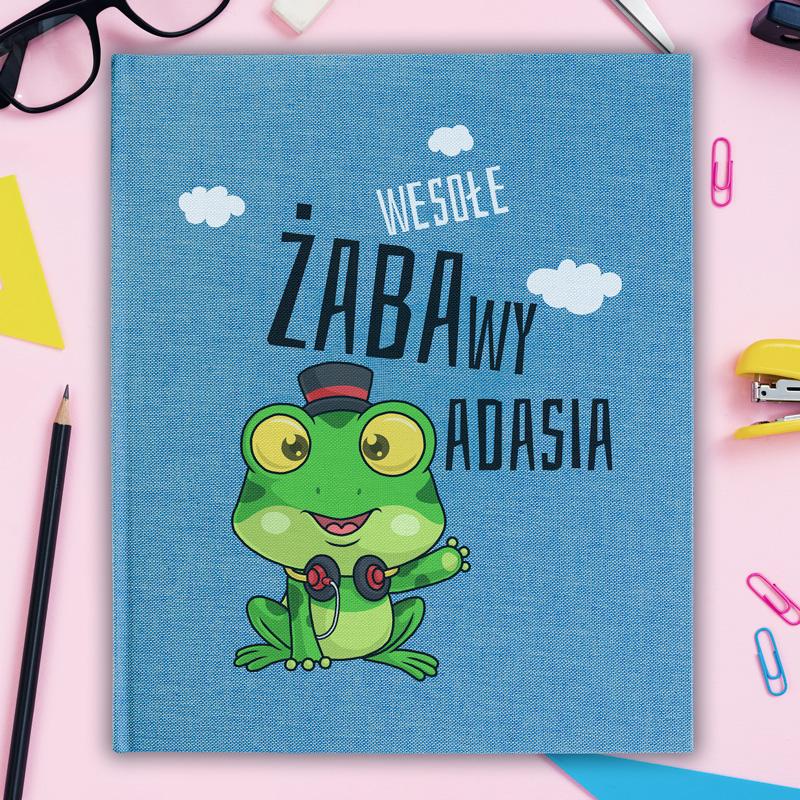 Personalizowany album na zdjęcia w niebieskim kolorze okładki oraz personalizowanym nadrukiem i obrazkiem Pana Żaby.