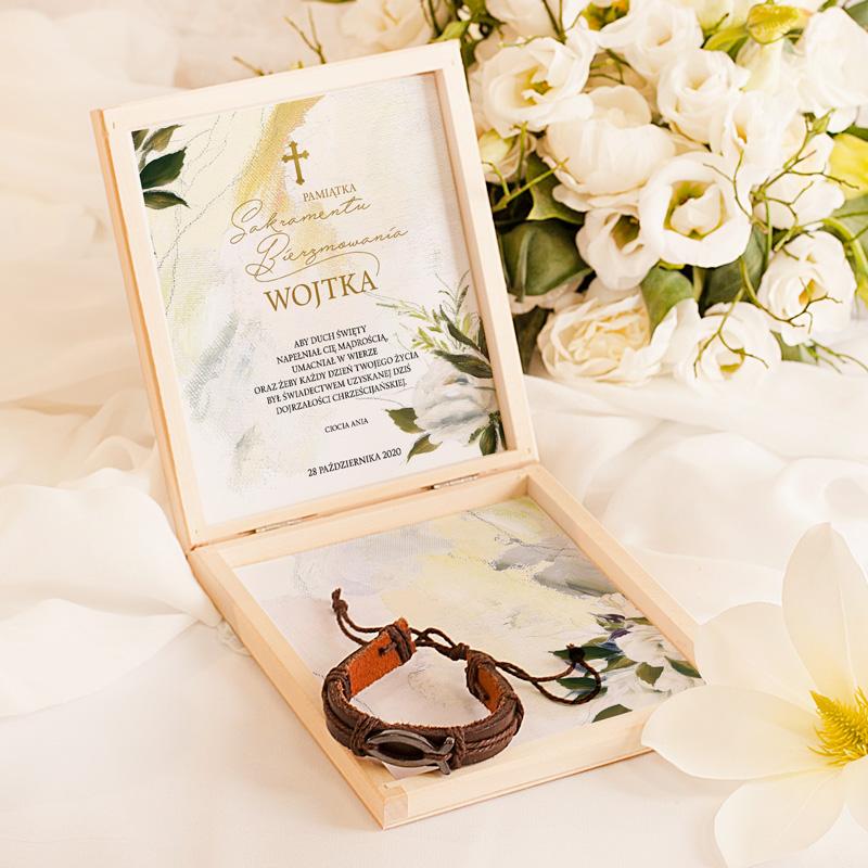 Drewniana szkatułka z personalizowaną dedykacją na ozdobnej karcie oraz skórzana bransoletka.