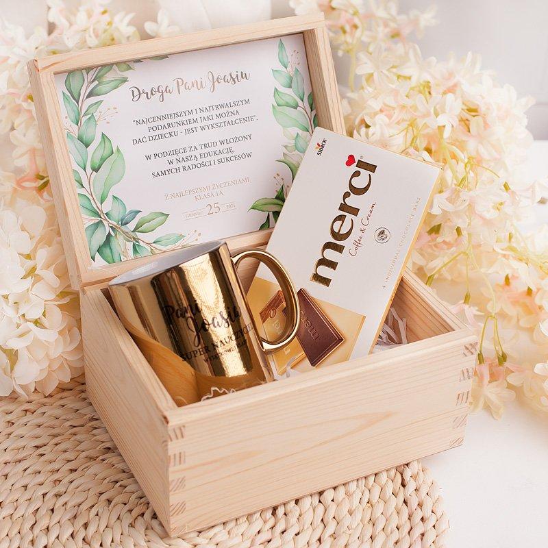 Skrzynka z naturalnego drewna ze złotym kubkiem oraz czekoladą Merci. Wewnątrz wieczka jest też personalizowana wklejka z życzeniami i podpisem.