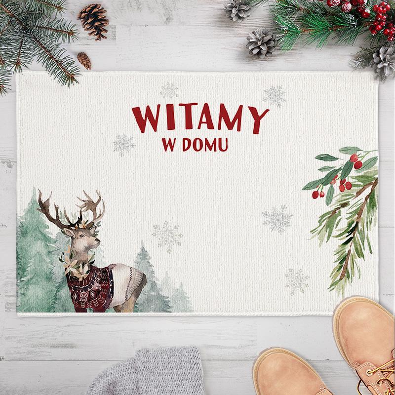 Dywanik świąteczny z nadrukiem renifera i gałązką ostrokrzewu. Na samym środku znajduje się czerwony napis Witamy w domu + miejsce na nazwisko.