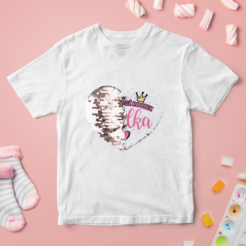 Koszulka z odwracanymi cekinami w białym kolorze. Na koszulce umieścimy cekinowe serduszko z imieniem.