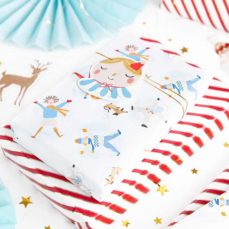 Papier prezentowy biały, na jego tle są dekoracje w postaci ludzików w zimowych strojach.