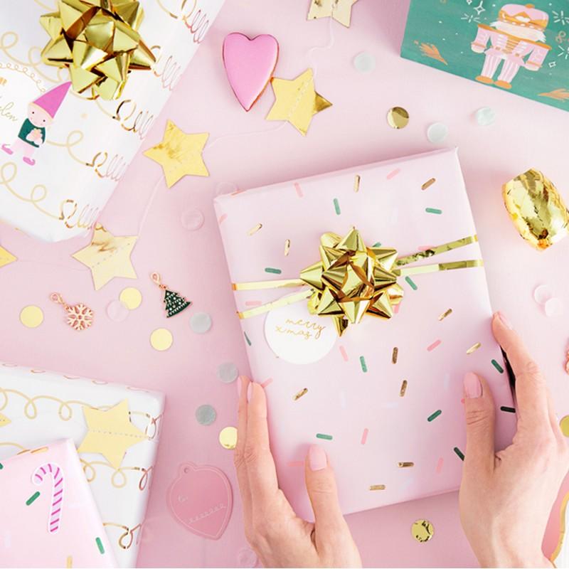 Papier do pakowania prezentów w zestawie dwóch rolek, w dwóch wzorach: różowy i biały z delikatnymi ozdobnikami.