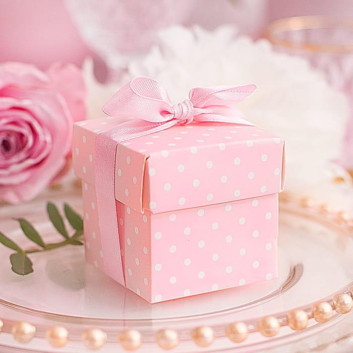 Komplet pudełek do prezentów dla gości. Na różowym tle wzór białych kropek.