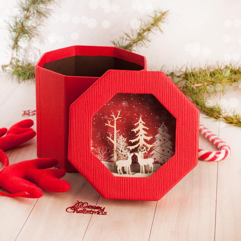Dekoracyjne pudełko na prezent świąteczny z dekoracyjną aplikacją na wieczku. W środku wieczka znajdują się drewniane aplikacje, które tworzą świąteczny obrazek.