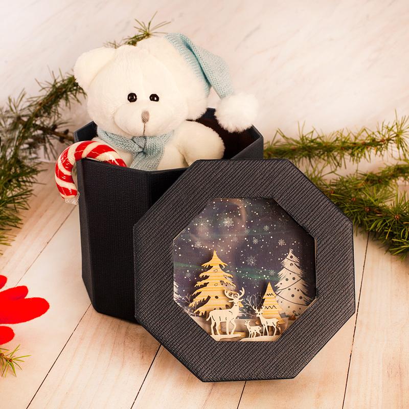 Zestaw upominków pod choinkę - miś pluszowy w czapce i szaliku, słodka, cukrowa laska oraz pudełko z wieczkiem, na którym jest świąteczny obrazek 3D.