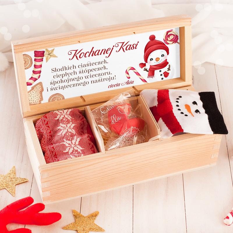 Drewniane pudełko w zestawie ze skarpetkami i życzeniami świątecznymi z grafiką bałwanka.