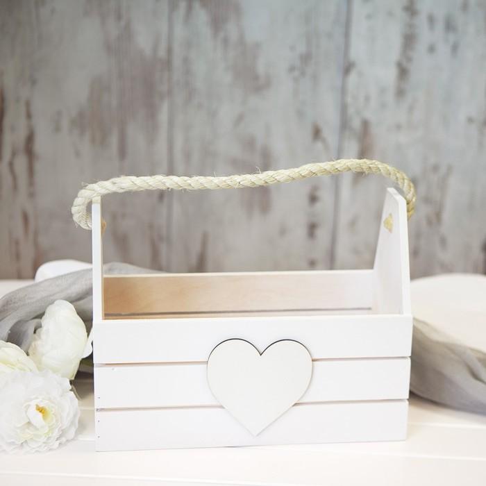 Drewniana skrzynia pomalowana na biało z sercem na froncie i grubym sznurem do noszenia. Idealna na opakowanie prezentu.
