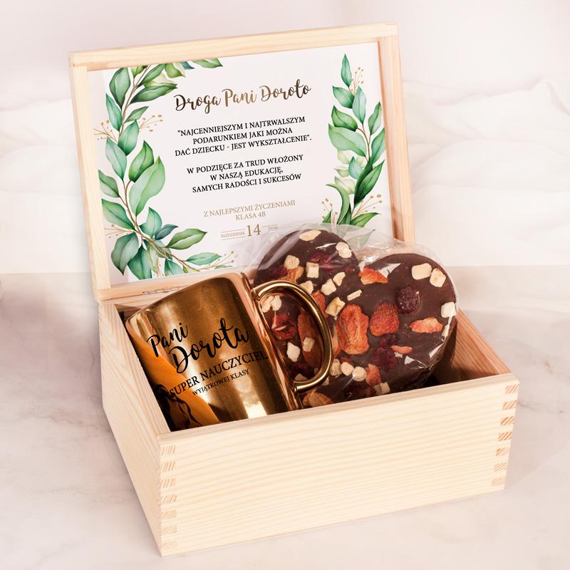 Skrzynka z naturalnego drewna ze złotym kubkiem oraz czekoladowym sercem z suszonymi owocami. Wewnątrz wieczka jest też personalizowana wklejka z życzeniami i podpisem.