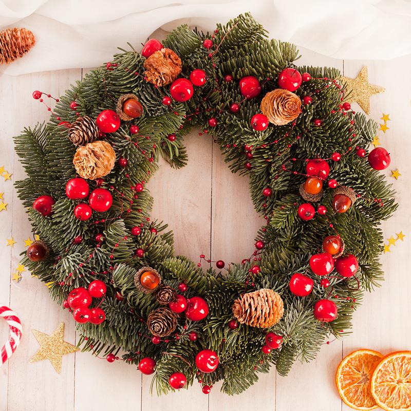 Stroik z żywej jodły z aplikacjami w bożonarodzeniowym stylu z czerwonymi koralikami oraz szyszkami.