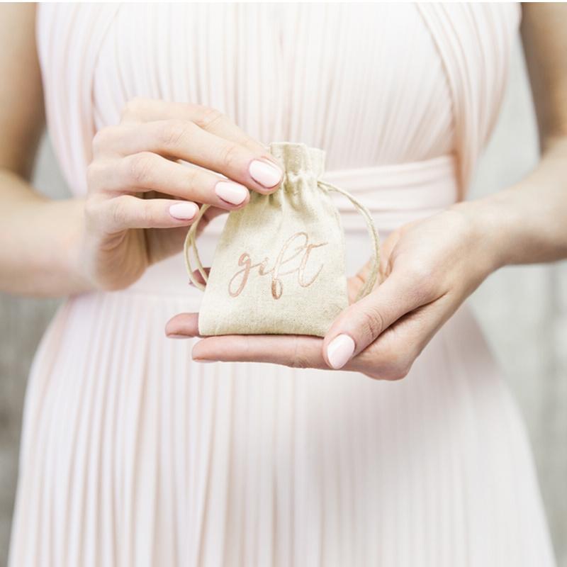 Woreczek bawełniany ze ściągaczem i napisem w kolorze różowe złoto GIFT.