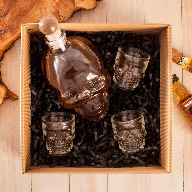Zestaw karafka i kieliszki - szklane w kształcie ludzkiej czaszki. Zestaw zapakowany jest w pudełko kartonowe z wieczkiem i czarnym konfetti na dnie.