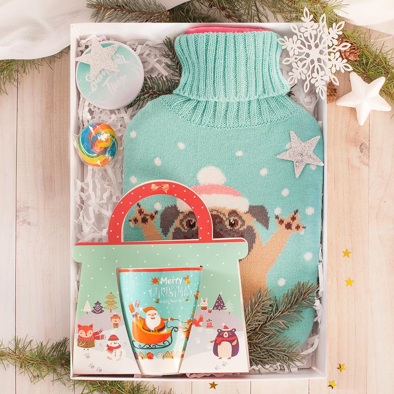 Zimowy prezent w białym pudle, kubek, termofor, lizak i lusterko.