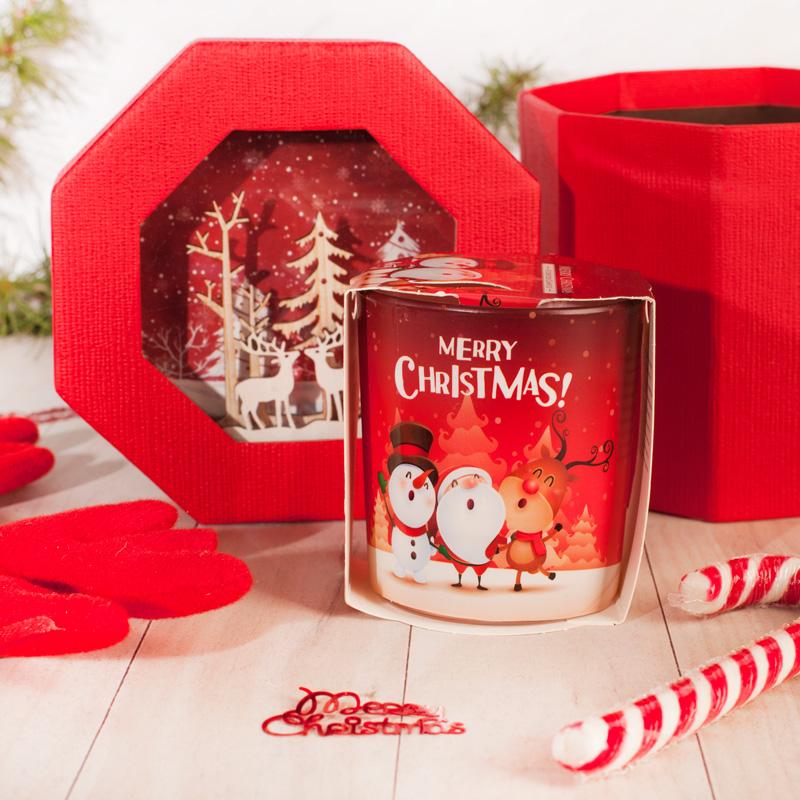 Świąteczny zestaw upominków w czerwonym, dekoracyjnym opakowaniu. Wewnątrz znajduje się zapachowa świeczka z zimową grafiką oraz świąteczna, cukrowa laska.