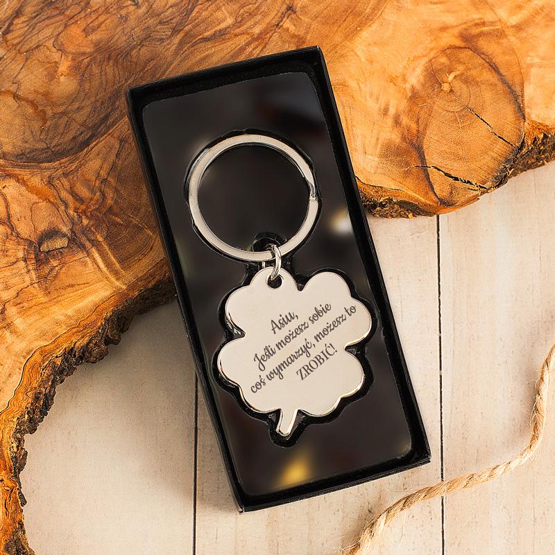 Personalizowany brelok do kluczy w kształcie koniczynki. W zestawie znajduje się również czarne pudełko.