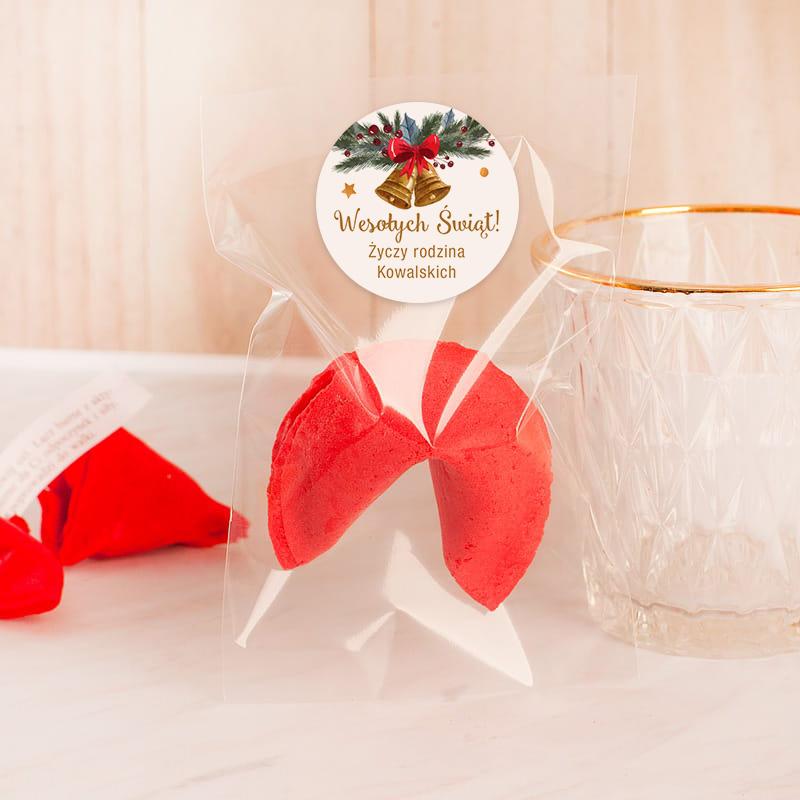 Ciasteczko z wróżbą w kolorze czerwonym z okrągłą etykietą z dzwoneczkiem i personalizowanym napisem z nazwiskiem rodziny.