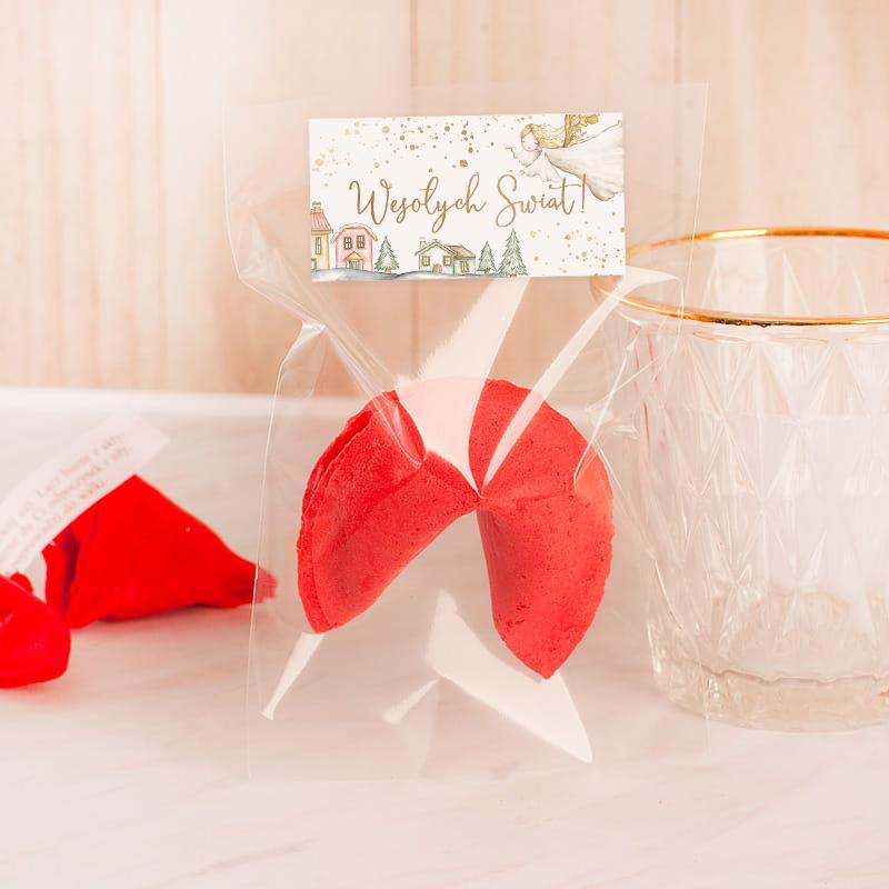 Ciasteczko świąteczne w kolorze malinowym z prostokątną etykietą z napisem Wesołych Świąt.