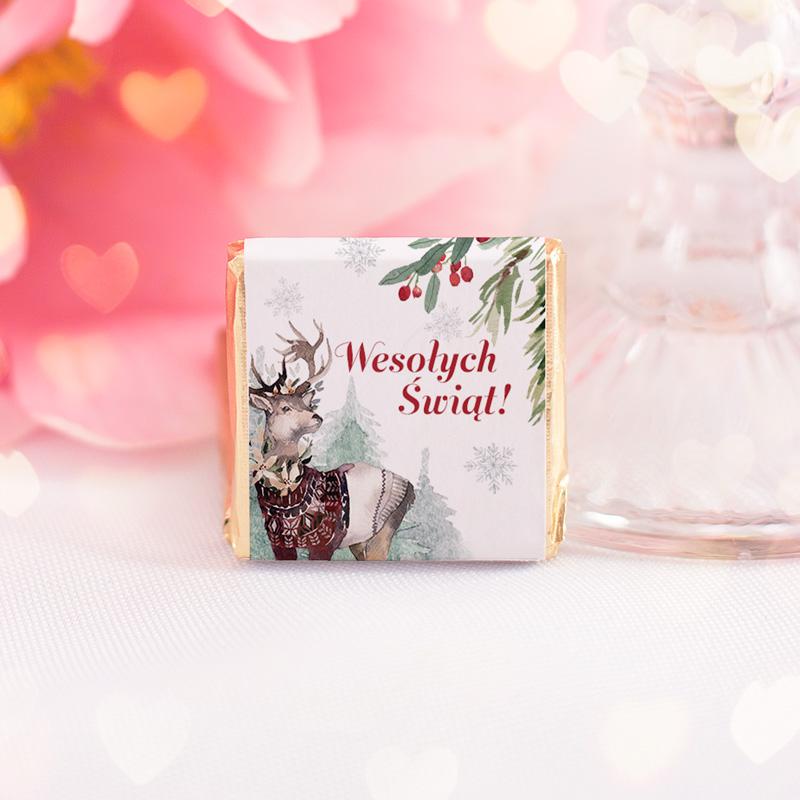 Czekoladka świąteczna z życzeniami na nowy rok. Na etykiecie jest jelonek i jemioła na tle zimowego lasu.