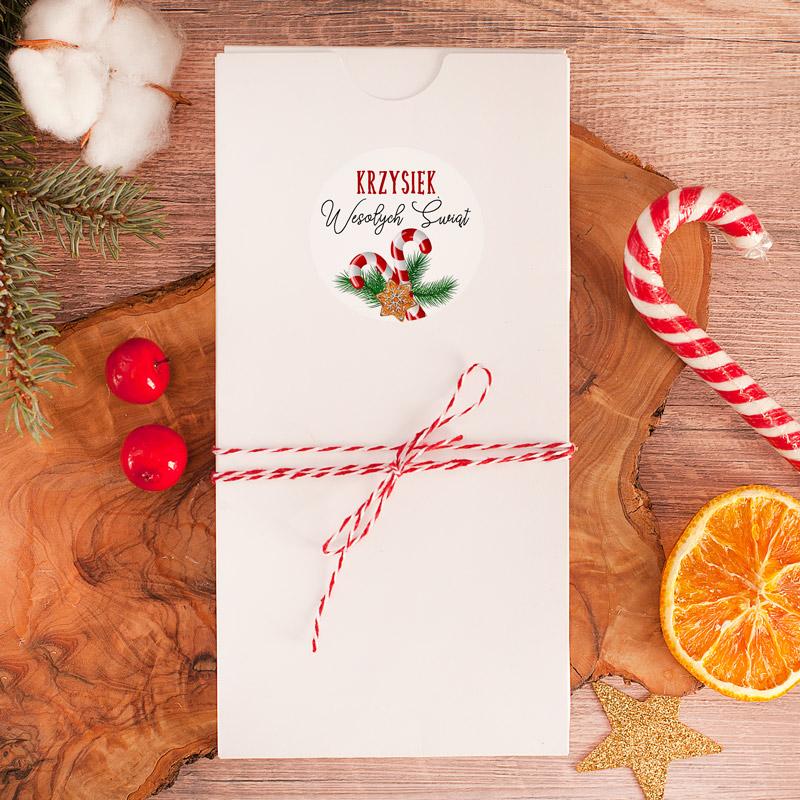 Białe opakowanie na czekoladę z personalizowaną etykietą na której znajduje się imię oraz stroik świąteczny. Całość dopełnia dekoracyjny sznureczek.