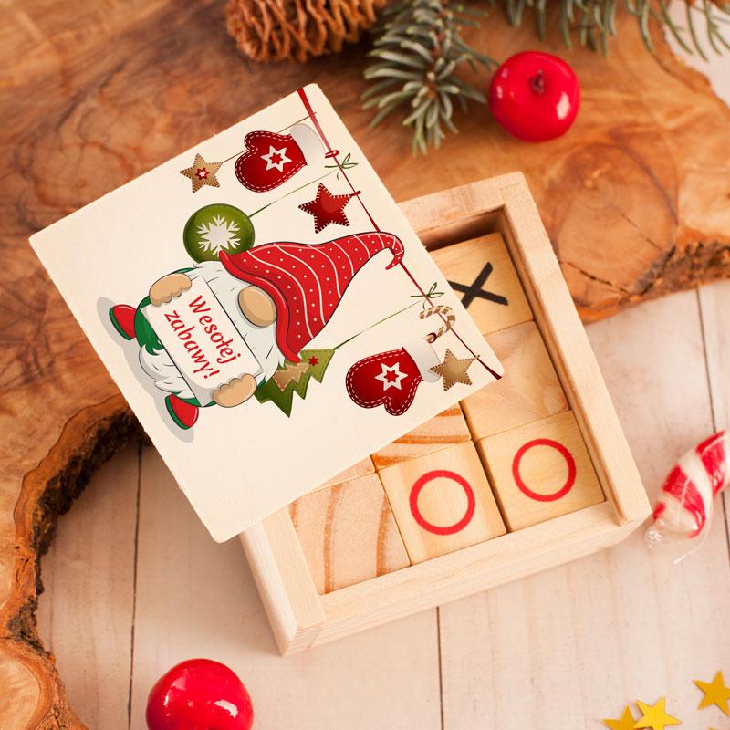 Gra towarzyska kółko i krzyżyk w drewnianym pudełku z nadrukiem na wieczku w postaci skrzata z tabliczką udanej zabawy.