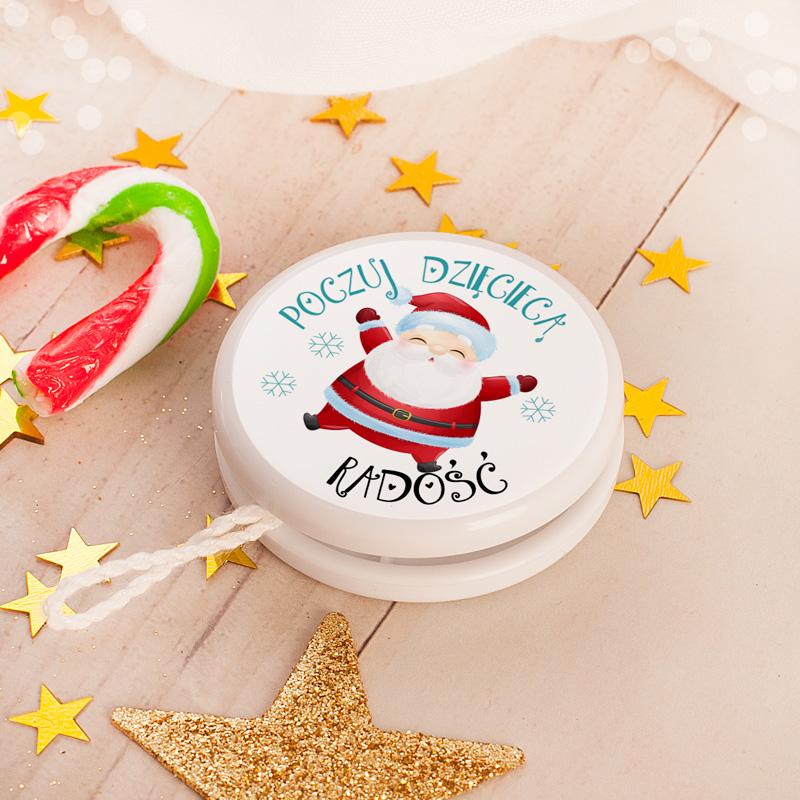 Jojo z okrągłą etykietą na której znajduje się św. Mikołaj oraz napis poczuj dziecięcą radość.