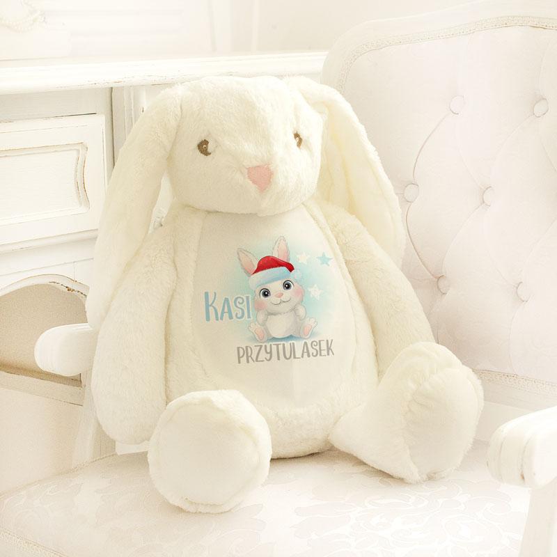 Zajączek pluszowy prezent dla dziecka na święta. Na brzuszku białej maskotki jest imię dziecka i rysunek kicusia.