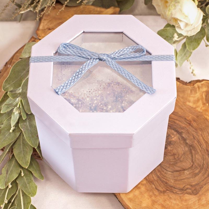 Ozdobne pudełko w błękitnym kolorze z dekoracją na wieczku w postaci niebieskiej kokardki.