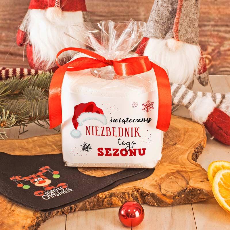 Niezbędnik świąteczny czyli prezent dla każdego. Papier toaletowy z etykietą świąteczną i czerwoną wstążką oraz maseczka ochronna na twarz czarna ze świątecznym obrazkiem po jednej stronie.