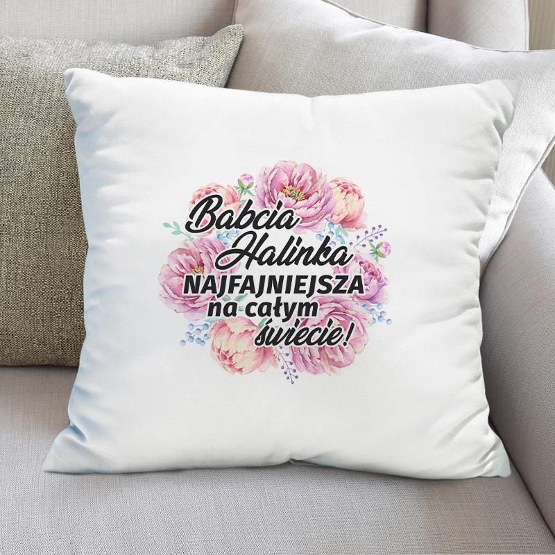 Poduszka z nadrukiem Babcia z imieniem Najfajniejsza na całym świecie oraz kwiatową grafiką. Poduszka ma kwadratowy kształt i biały kolor poszewki.
