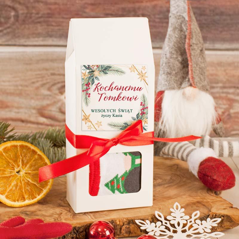 Skarpetki chłopięce w motyw ze świętym Mikołajem, które zapakowane są w biały kartonik z czerwoną wstążką oraz bilecikiem z życzeniami na Boże Narodzenie.