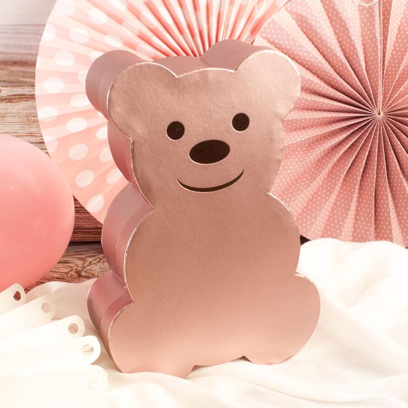 Pudełko w kształcie misia jako opakowanie na prezent. Pudło ma kolor różowego złota i przyjazny uśmiech.