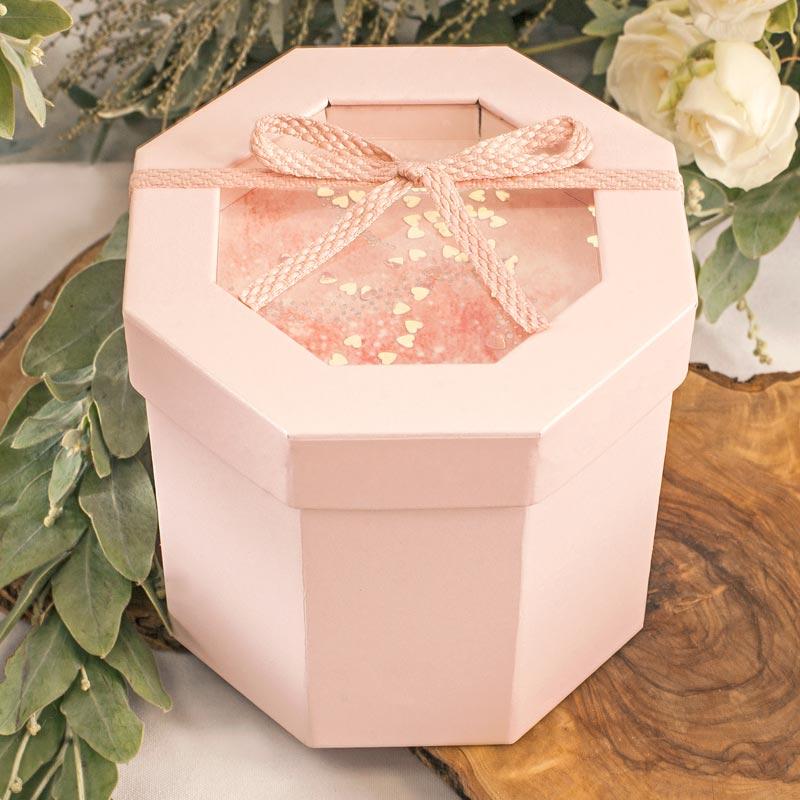Różowe pudełko w kształcie walca z dekoracją na wieczku i różową wstążką.