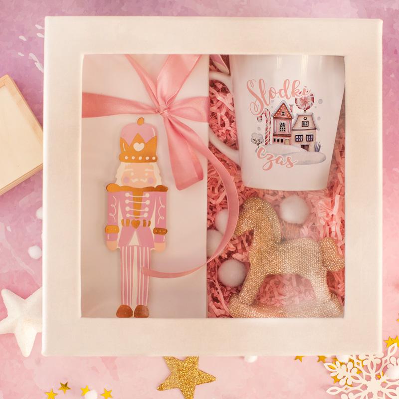 Różowy zestaw w welurowym pudełku z kubkiem w środku, czekoladą w różowym opakowaniu, ze złotym konikiem i grą kółko i krzyżyk.