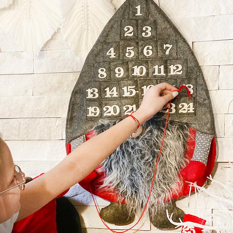 Kalendarz adwentowy w postaci materiałowego skrzata, który na dużej czapce z filcu, na którym znajdują się kieszonki z numeracją.