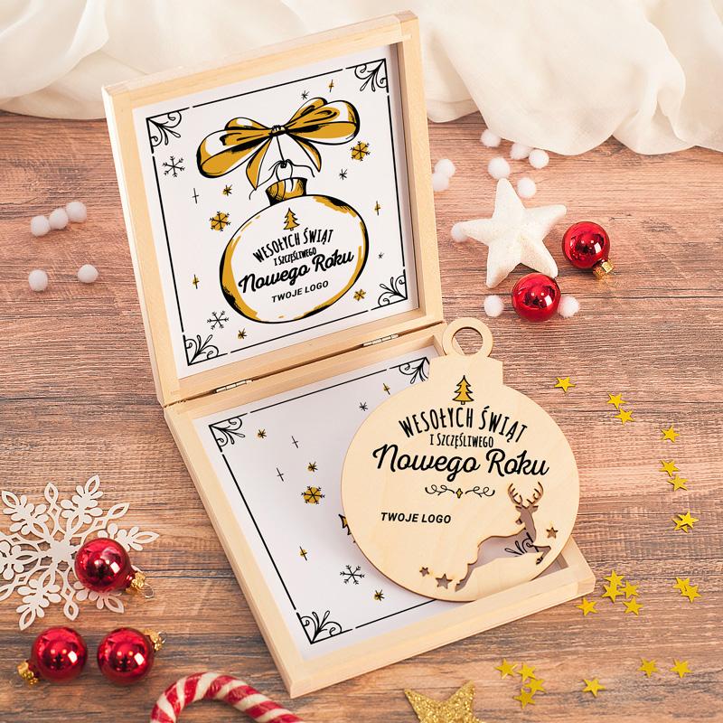 Drewniana skrzyneczka w świątecznym wydaniu. W środku jest biała etykieta z ramką, płatkami śniegu i dużym rysunkiem żółtej bombki. W pudełku jest upominek drewniana bombka z Twoim logo lub podpisem. Gotowe do wręczenia pudełko świąteczne.