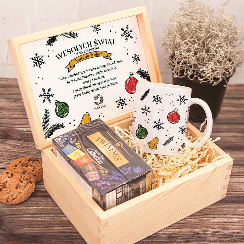 Skrzynka świąteczna prezent dla pracowników firmy. W drewnianej skrzyni jest kubek a na nim bombki i płatki śniegu. W zestawie pyszna herbata. Na wieczku jest personalizowana etykieta z życzeniami na święta i nowy rok oraz miejsce na logo firmy.