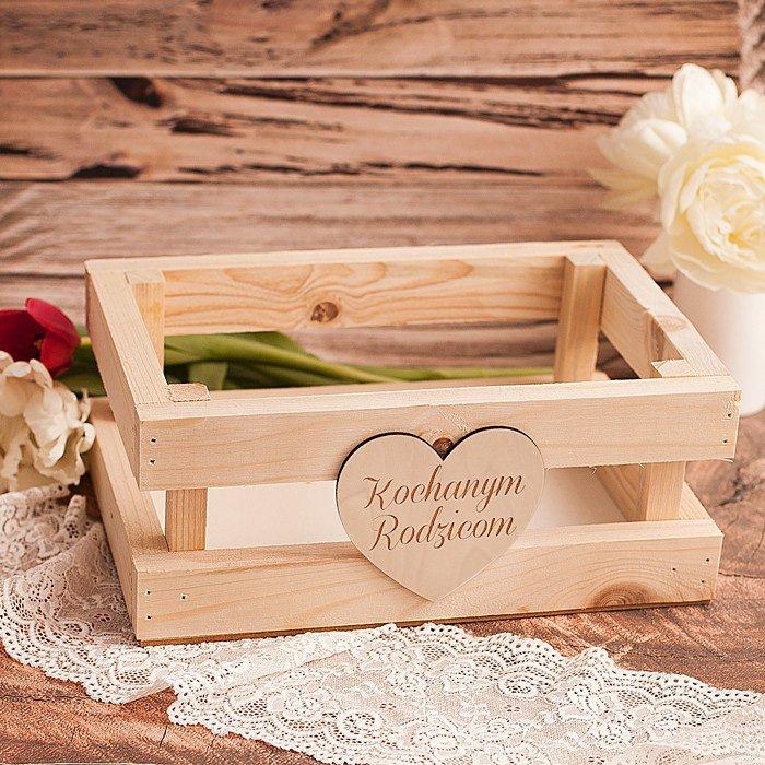 Drewniana skrzynia do wypełnienia upominkami z drewnianym sercem na froncie, na którym znajduje się grawer Kochanym rodzicom.